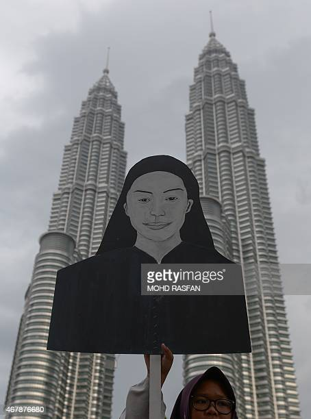 A supporter of Malaysia's opposition leader Anwar Ibrahim holds a cardboard figure of Altantuya Shaariibuu a Mongolian national murdered in 2006 amid...