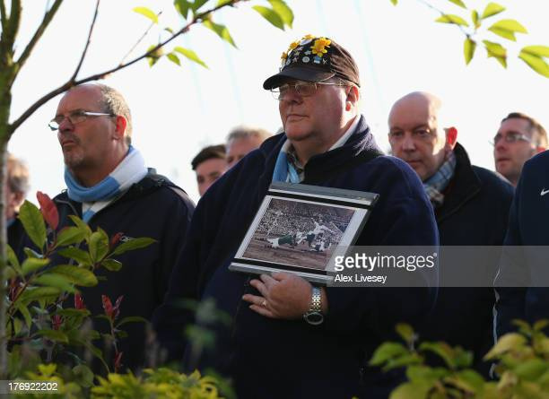 A supporter of Manchester City holds a photograph of Bert Trautmann in memory of the former goalkeeper who died in July during a memorial service...