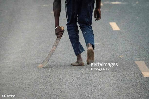 A supporter of National Super Alliance holding a machete reacts towards police officers during a protest against Kenya's second poll in Kisumu on...