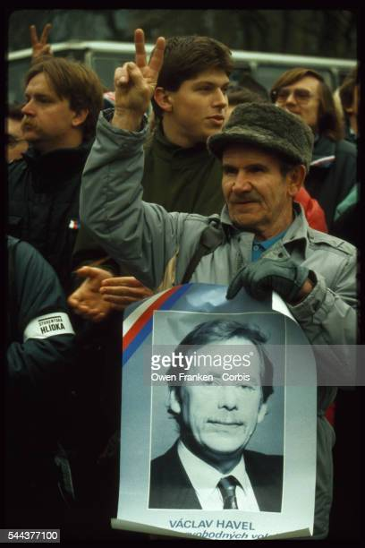 A supporter of new Czech president Vaclav Havel shows a 'V' sign for victory and a poster of Havel on the day after Havel's election by the National...