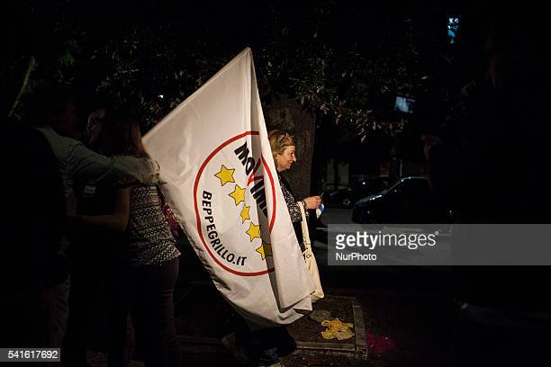 A supporter of newly elected mayor of Rome Five Star Movement's candidate Virginia Raggi holds a flag after the winning of the mayoral election on...