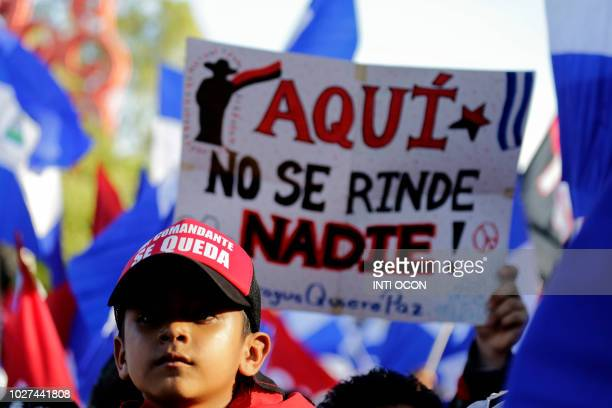 A supporter of Nicaraguan President Daniel Ortega holds a sign reading Here nobody surrenders during a rally in Managua on September 5 2018 Ortega...