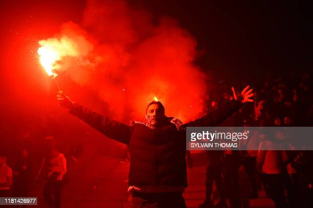 A supporter of Olympique de Marseille holds a flare in front of the Velodrome stadium to celebrate the club's 120th birthday prior to the French L1...