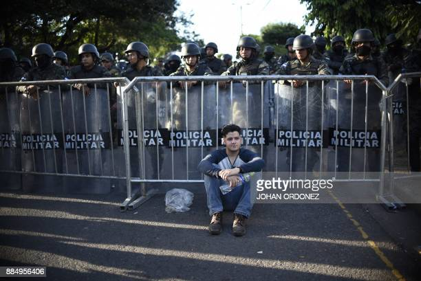 TOPSHOT A supporter of opposition candidate Salvador Nasralla rests next to a group of Honduran military police after a march held on December 3 2017...