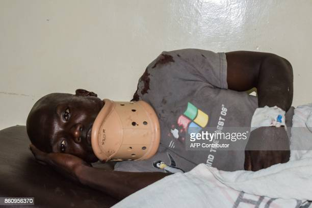 A supporter of opposition coalition the National Super Alliance who had been shot in his neck during the nation wide protest lies down on a bed at...