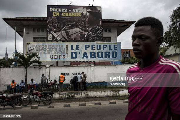 A supporter of opposition presidential candidate Felix Tshisekedi stands in front of the The Union for Democracy and Social Progress house in...