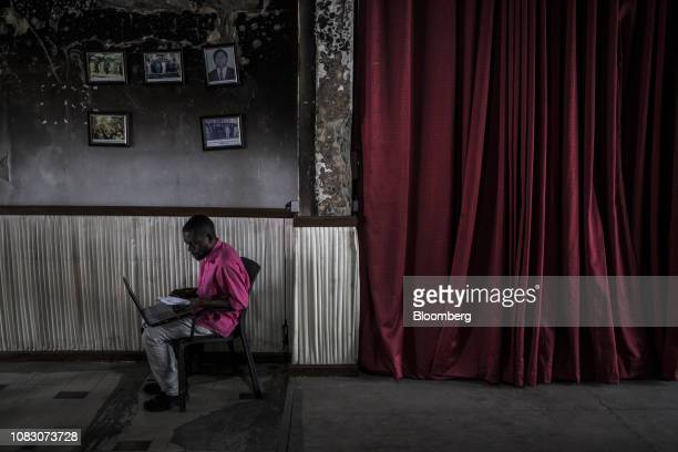 A supporter of opposition presidential candidate Felix Tshisekedi works on a laptop computer inside the The Union for Democracy and Social Progress...