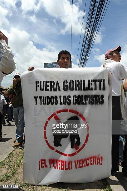 A supporter of ousted Honduran President Manuel Zelaya holds a sign reading Get out Goriletti and all involved in the coup The people will overcome...