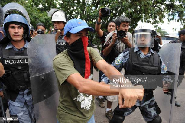 A supporter of ousted Honduran President Manuel Zelaya stands in front of soldiers in riot gear and police during a clash between marchs of...