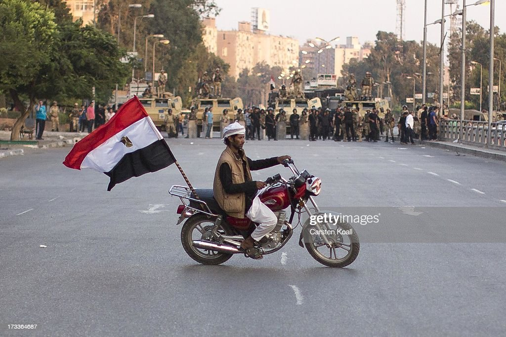 A supporter of ousted president Mohamed Morsi drives his motorbike in front of a Egyptian Army barrier near the headquarters of the Egyptian Republican Guard following Friday prayers on the third day of Ramadan on July 12, 2013 in Cairo, Egypt. Egypt continues to be in a state of political paralysis following the ousting of former President and Muslim Brotherhood leader Mohamed Morsi by the military. Adly Mansour, chief justice of the Supreme Constitutional Court, was sworn in as the interim head of state in a ceremony in Cairo on the morning of July 4.