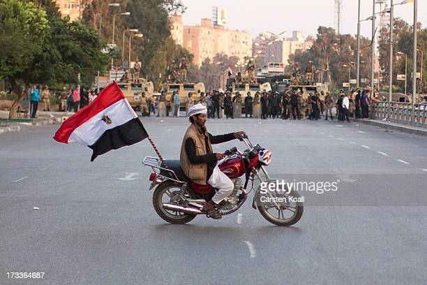 A supporter of ousted president Mohamed Morsi drives his motorbike in front of a Egyptian Army barrier near the headquarters of the Egyptian...