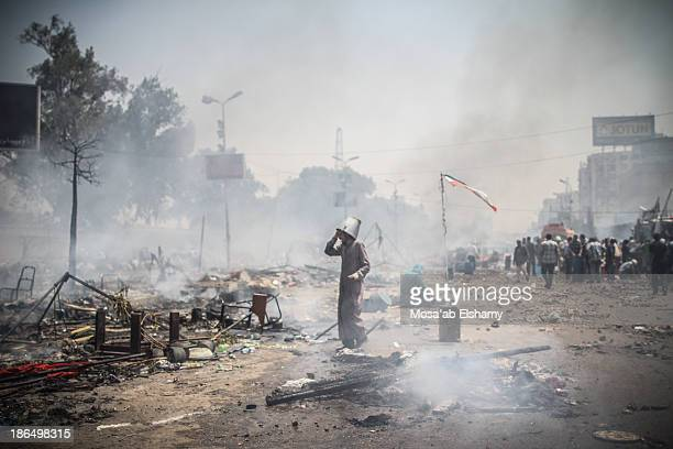 Supporter of ousted president Mohamed Morsi is seen with a bucket on his head as helmet during the violent dispersal of Rabaa Adaweya camp by...