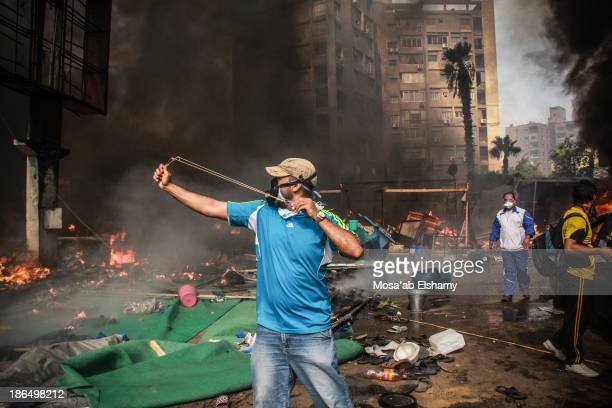 CONTENT] A supporter of ousted president throws rocks with a sling during the violent dispersal of Rabaa Adaweya camp by security forces on August...