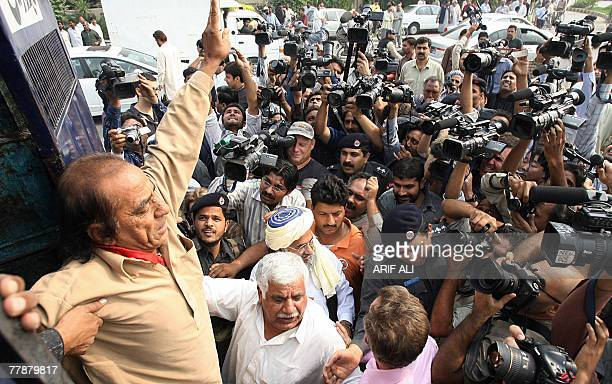 A supporter of Pakistan People's Party of former premier Benazir Bhutto shows victory after arresting by police near a house where she is staying in...