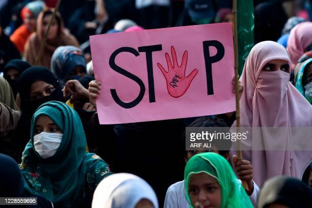 """Supporter of Pakistani Islamic political party Jamaat-e-Islami holds a placard reading """"Stop"""" during a protest against an alleged gang rape of a..."""
