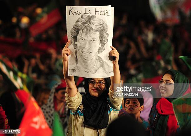 A supporter of Pakistani opposition politician Imran Khan holds a drawing depicting him during an antigovernment protest outside the parliament in...