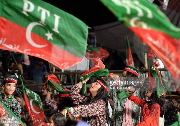 A supporter of Pakistani opposition politician Imran Khan wave Pakistan Tehreek Insaf party flags during an antigovernment protest outside the...