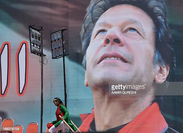 Supporter of Pakistani politician and former cricketer Imran Khan walks onto a stage next to an electoral poster of Khan at the venue of an election...