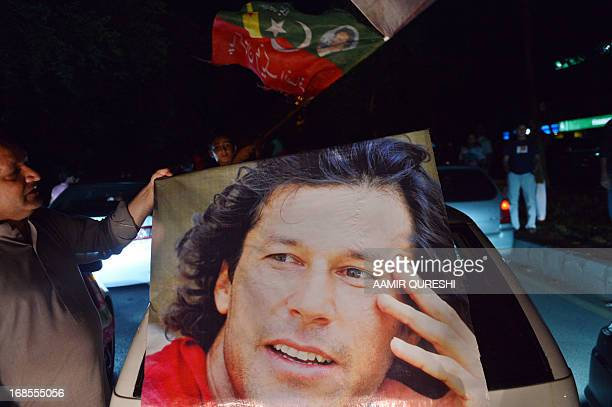 A supporter of Pakistani politician and former cricketer Imran Khan carries his portrait as they take part in a rally in Islamabad on May 11 2013 in...