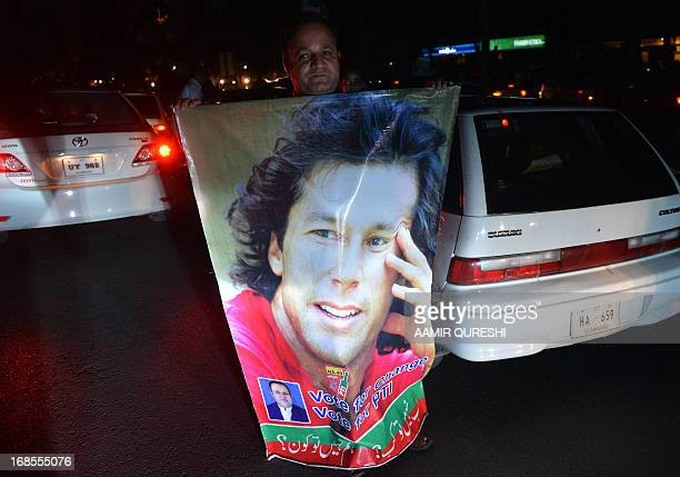 Supporter of Pakistani politician and former cricketer Imran Khan carries his portrait as they take part in a rally in Islamabad on May 11, 2013 in...