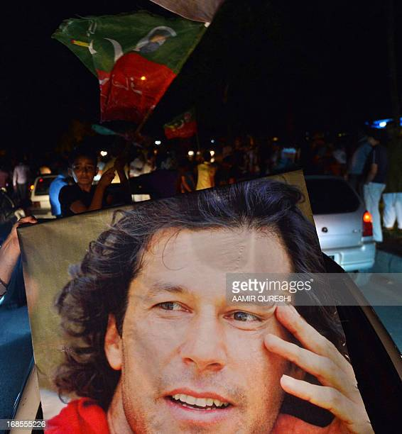 Supporter of Pakistani politician and former cricketer Imran Khan carries his portrait during a rally in Islamabad on May 11, 2013 in Pakistan's...