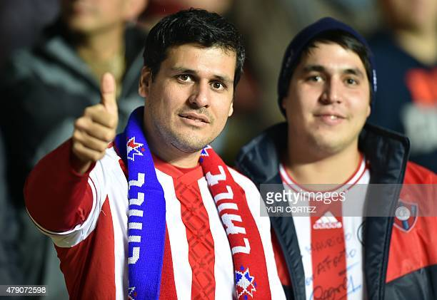 Supporter of Paraguay wearing a scarf of Chile gives the thumb up before the start of the Copa America semifinal football match against Argentina in...