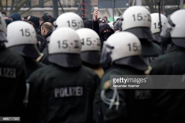 A supporter of Pegida gestures towards police forces during a public gathering on March 14 2015 in Wuppertal Germany Several hundred Salafis who in...