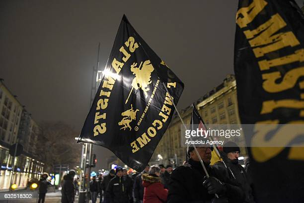 A supporter of Pegida holds a flag during a protest at the Neumarkt Square in Dresden Germany on January 23 2017