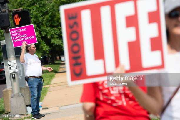 A supporter of Planned Parenthood stands near an antiabortion demonstrators as they hold a protest outside the Planned Parenthood Reproductive Health...