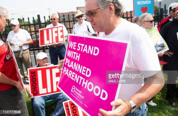 A supporter of Planned Parenthood walks past antiabortion demonstrators as they hold a protest outside the Planned Parenthood Reproductive Health...