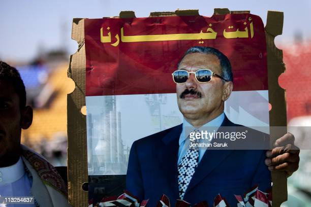 A supporter of President Ali Abdullah Saleh hold up a picture of the president after he gave a speech to a packed stadium on March 10 2011 in Sana...