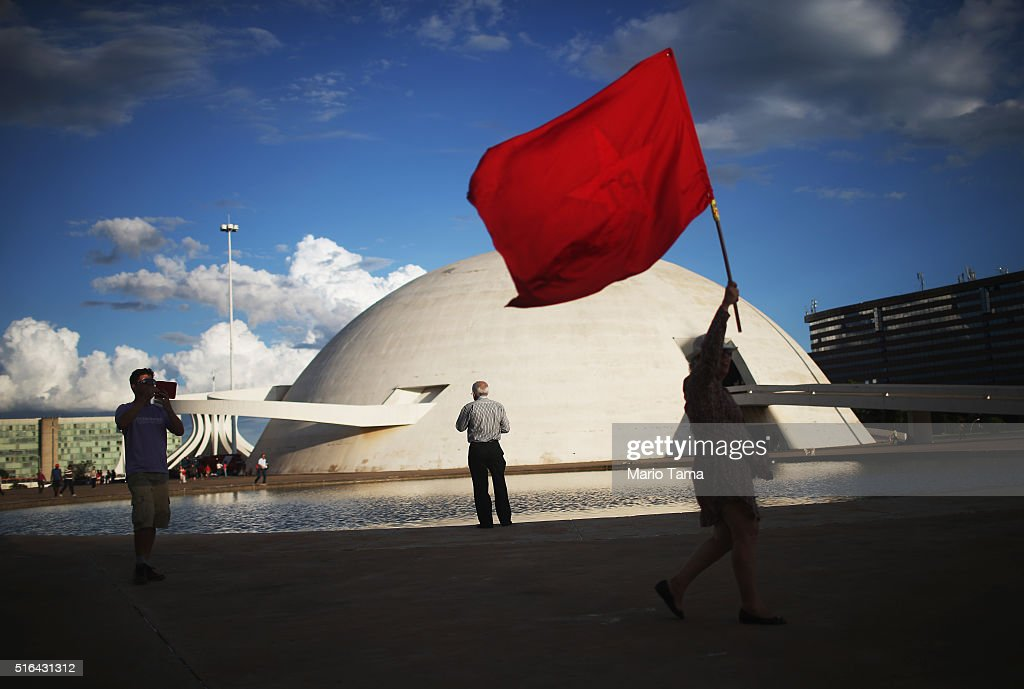 A supporter of President Dilma Rousseff and former President Luiz Inacio Lula da Silva carries a Worker's Party flag to a demonstration at Esplanada dos Ministerios in March 18, 2016 in Brasilia, Brazil. A Brazilian court ruled that 'Lula' could begin work as chief of staff for current President Dilma Rousseff.
