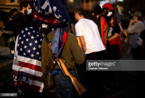 Supporter of President Donald Trump carries a rifle as people gather outside the Governor's Mansion on November 7, 2020 in St Paul, Minnesota. Around...