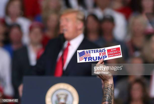A supporter of President Donald Trump holds up a bumper sticker as the president speaks during a rally at the International Air Response facility on...