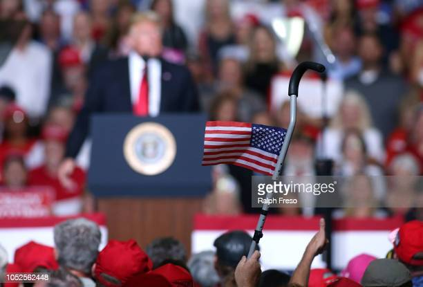 A supporter of President Donald Trump waves an american flag attached to a walking cane as the president speaks during a rally at the International...