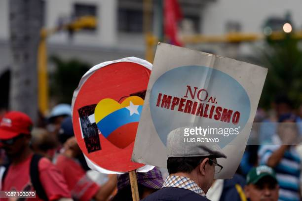 A supporter of President Nicolas Maduro's government holds a sign reading No to imperialism while taking part in a march on the anniversary of 1958...