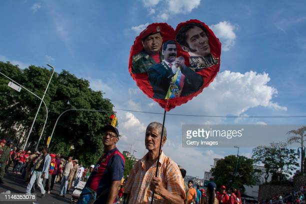 A supporter of president Nicolás Maduro holds a sign with the pictures of Hugo Chavez Nicolás Maduro and Simon Bolivar during a demonstration on May...