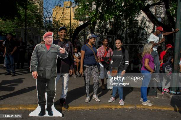 A supporter of president Nicolás Maduro smiles next to a lifesized cardboard photo of former late president Hugo Chavez during a demonstration on May...