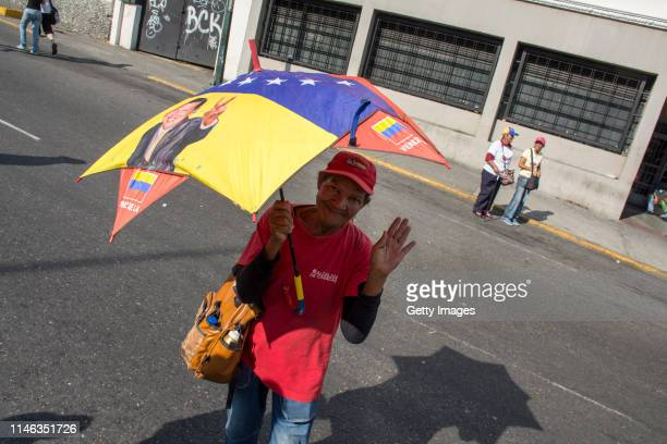 A supporter of president Nicolás Maduro waves with an Venezuelan colors umbrella during a demonstration on May 01 2019 in Caracas Venezuela Yesterday...