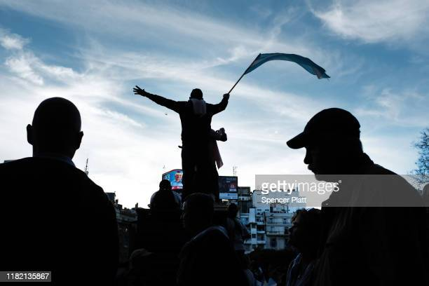 Supporter of President of Argentina Mauricio Macri waves a flag as he speaks during the closing presidential campaign rally called 'La Marcha del...