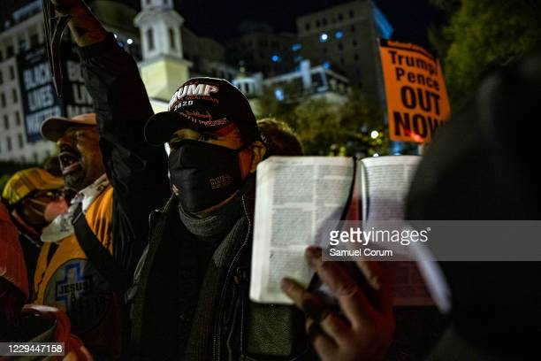 Supporter of President Trump holds up a bible as he is surrounded at Black Lives Matter Plaza in front of the White House on Election Day, November...