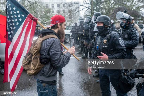 Supporter of President Trump speaks with riot police during a protest on January 6, 2021 in Salem, Oregon. Trump supporters gathered at state...