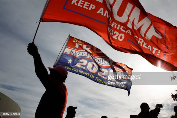 A supporter of President Trump waves flags outside of McKenzie Arena where US President Donald Trump is holding a rally in support of Republican...