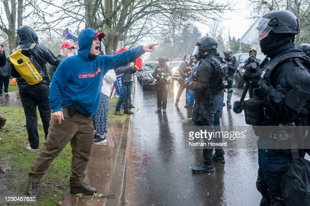 Supporter of President Trump yells at a line of riot police after violence erupted at a protest on January 6, 2021 in Salem, Oregon. Trump supporters...