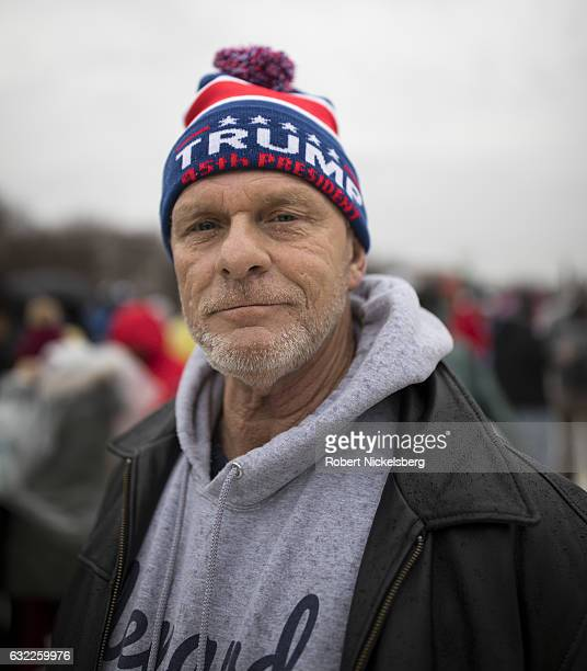 A supporter of Presidentelect Donald J Trump waits for the inauguration ceremony January 20 2017 in Washington DC Protestors and supporters gathered...