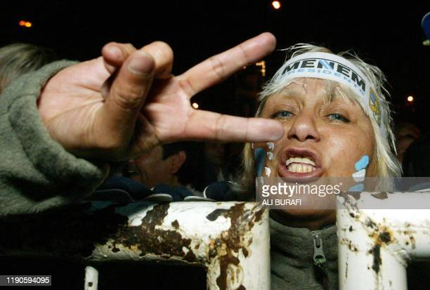 A supporter of presidential candidate Carlos Menem gestures to make a V for victory sign 27 April 2003 in Buenos Aires AFP PHOTO/Ali BURAFI Una...