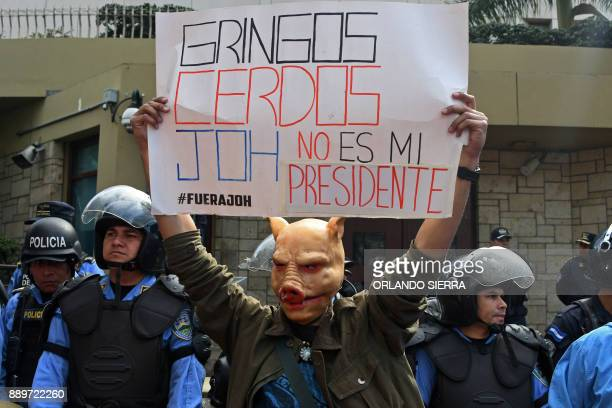 A supporter of presidential candidate for Honduras' Opposition Alliance against Dictatorship Salvador Nasralla wearing a pig mask demonstrates in...