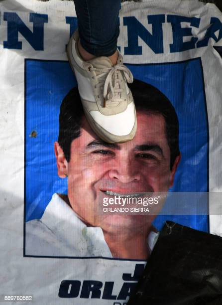 A supporter of presidential candidate for Honduras' Opposition Alliance against Dictatorship Salvador Nasralla steps on a campaign poster of Honduran...