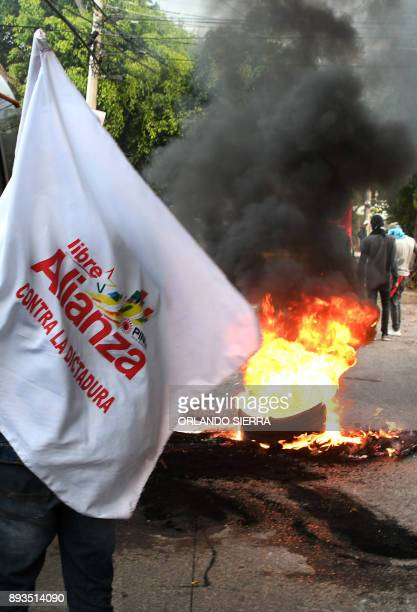 A supporter of presidential candidate for the Opposition Alliance against Dictatorship party Salvador Nasralla holds a flag next to a burning...
