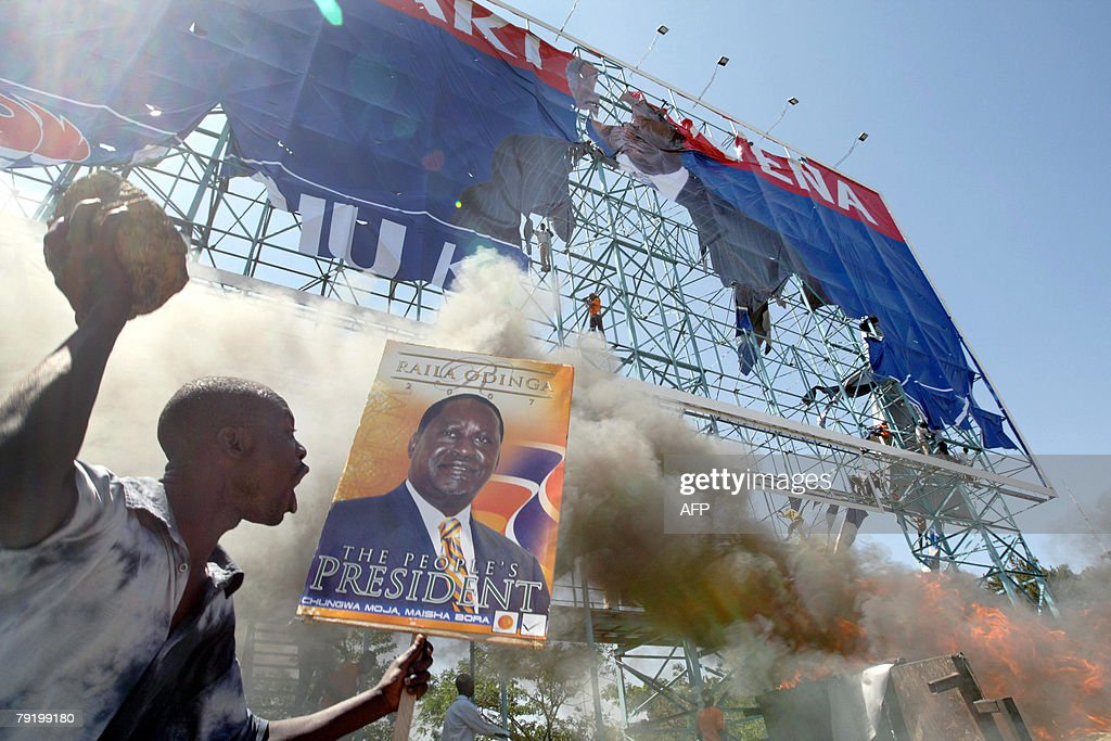 A supporter of presidential candidate Raila Odinga holds a rock as others burn a partially destroyed billboard of opposition presidential candidate and current Kenyan President Mwai Kibaki in Nairobi, 24 December 2007. Clashes between youth, each fielding popuplar presidential candidates, were broken up by police who fired tear gas to quell the melee that erupted after after supporters coming from the final rallies of both parties in the run-up to the Kenyan general election on December 27 encountered each other during rallies in the Kenyan capital.